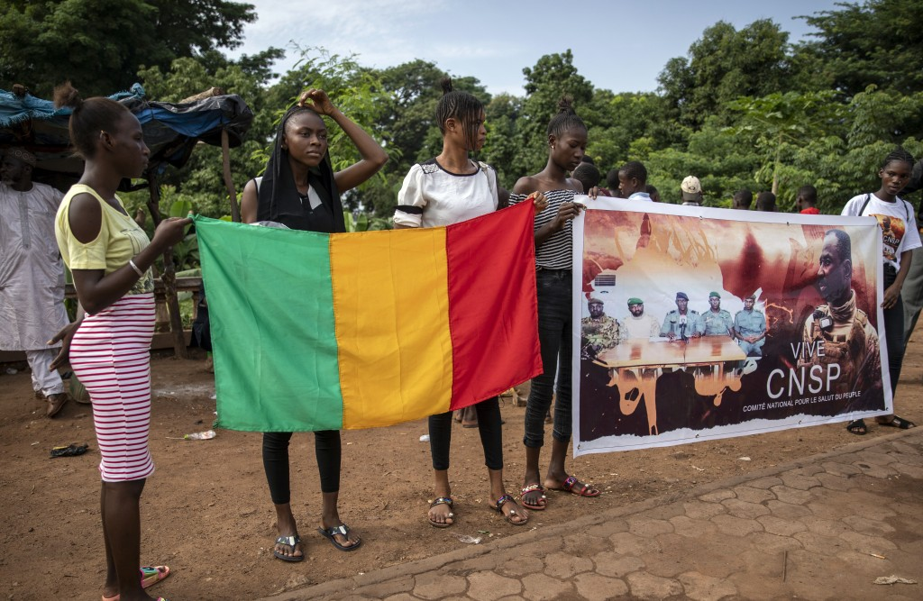 People hold a banner showing Col. Assimi Goita, leader of the junta which is now running Mali and calls itself the National Committee for the Salvatio...