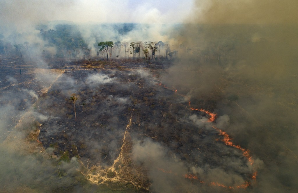 FILE - In this Aug. 23, 2020, file photo, fire consumes land recently deforested by cattle farmers near Novo Progresso, Para state, Brazil. Climate-co...