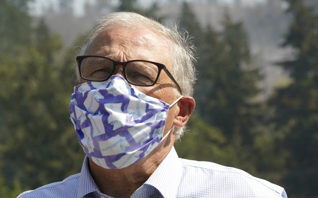 Washington Gov. Jay Inslee wears a mask as he talks to reporters, Wednesday, Sept. 9, 2020, following a tour to survey wildfire damage in Bonney Lake,...