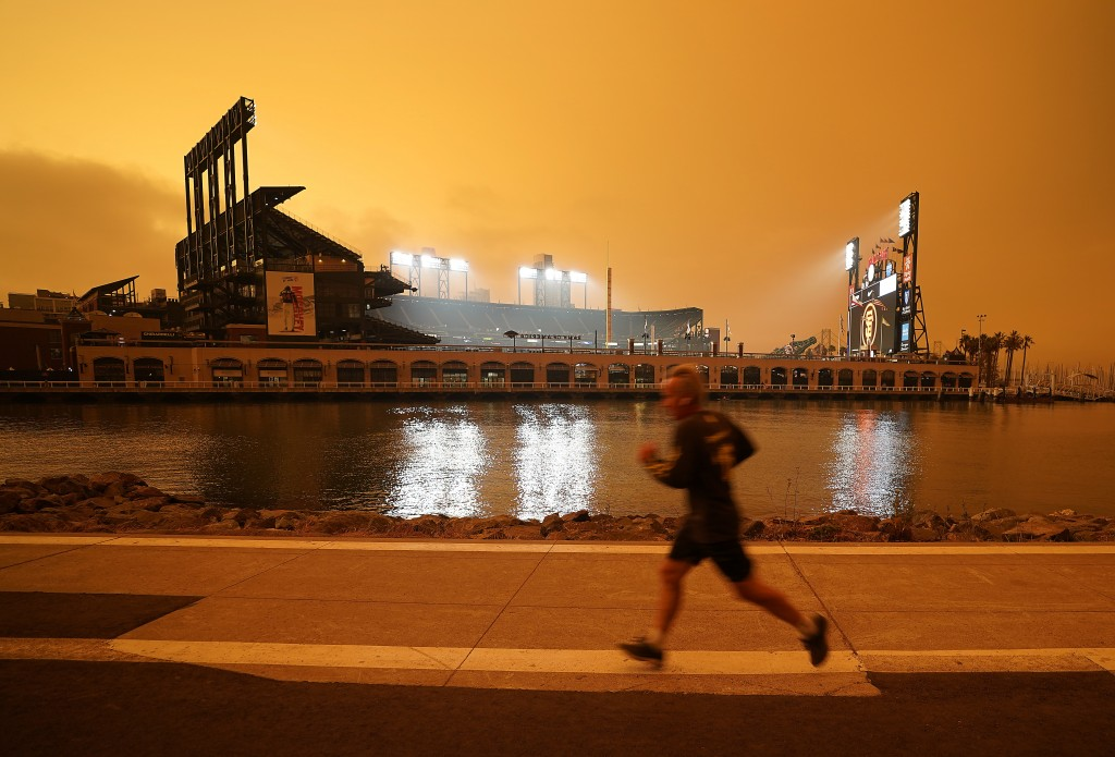 Under darkened skies from wildfire smoke, a jogger makes his way along McCovey Cove outside Oracle Park on Wednesday, Sept. 9, 2020, in San Francisco....