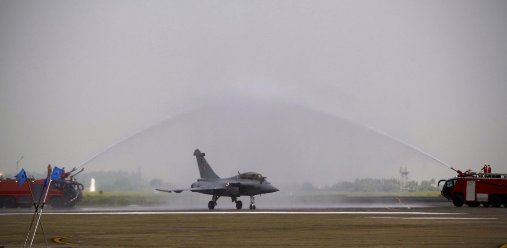 Water is sprayed on a French-made Rafale fighter jet during its induction ceremony at the Indian Air Force Station in Ambala, India, Thursday, Sept.10...