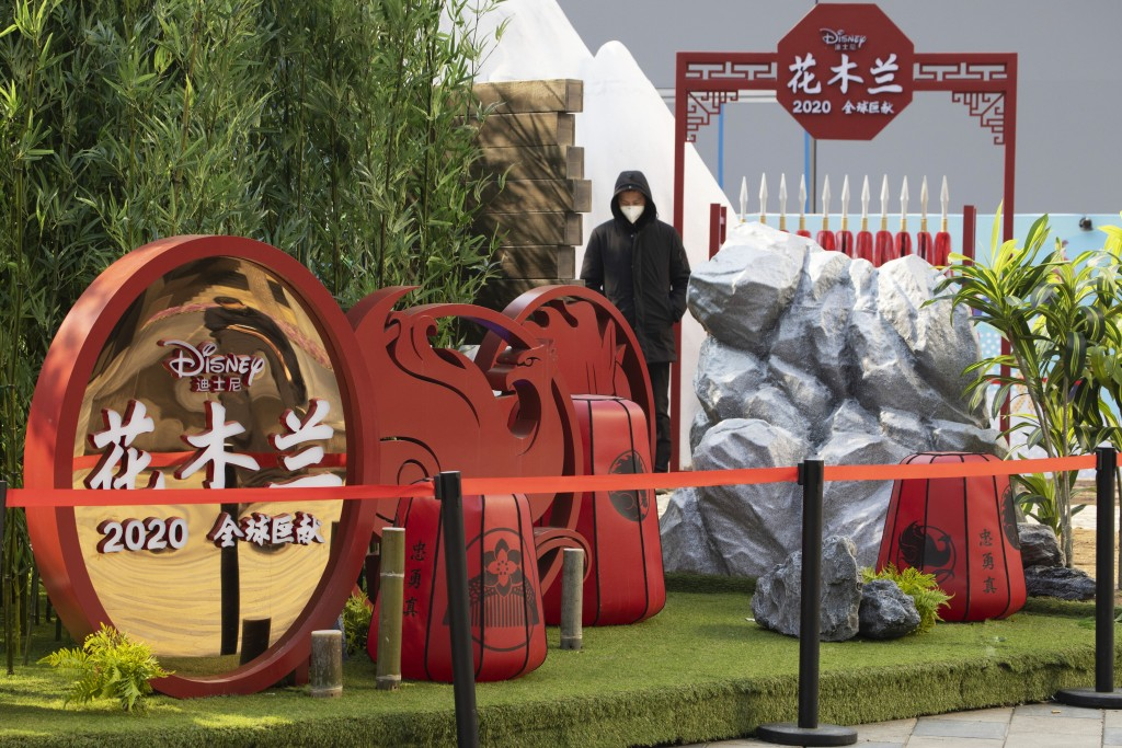 """A man watches over a set promoting the Disney movie """"Mulan"""" in Beijing on Wednesday, Feb. 19, 2020. Disney is under fire for filming part of its live-..."""