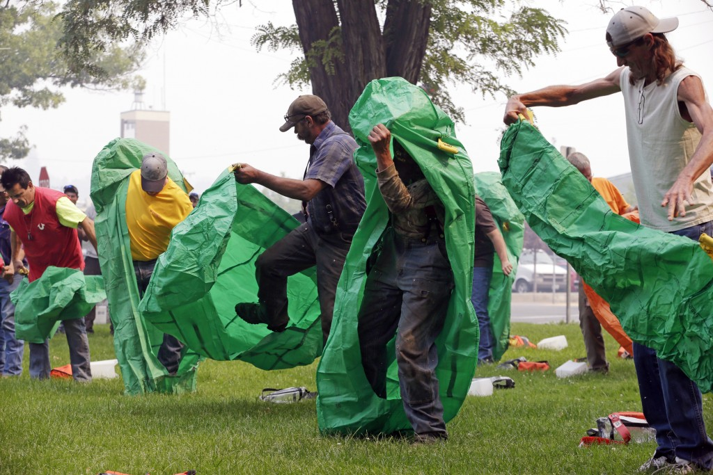 FILE - In this Aug. 22, 2015 file photo, volunteers learn to deploy fire shelters with practice equipment after a callout by fire officials seeking to...