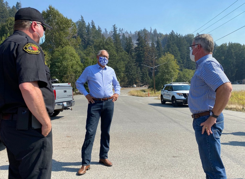 Washington Gov. Jay Inslee, center, talks to East Pierce Fire & Rescue Chief Bud Backer, left, and Pierce County Executive Bruce Dammeier about wildfi...