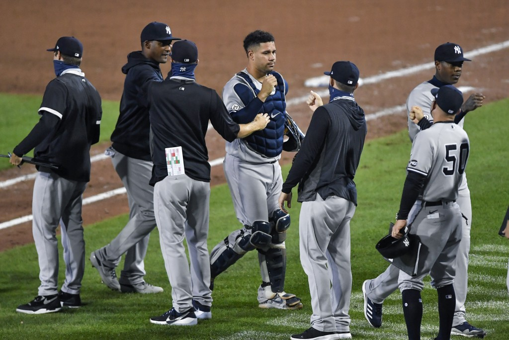New York Yankees catcher Gary Sánchez, center, and teammates celebrate a 7-2 win over the Toronto Blue Jays in a baseball game in Buffalo, N.Y., Wedne...