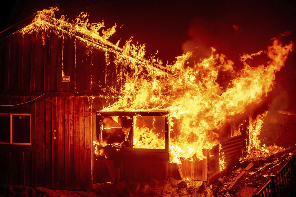 Flames shoot from a home as the Bear Fire burns through the Berry Creek area of Butte County, Calif., on Wednesday, Sept. 9, 2020. The blaze, part of ...