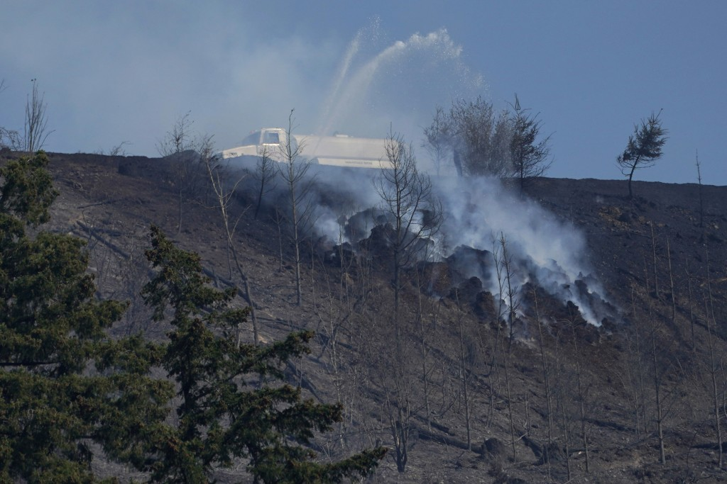 A tanker truck sprays water on a persistent hotspot of a wildfire on a ridge, Wednesday, Sept. 9, 2020, near Bonney Lake, Wash., south of Seattle. (AP...
