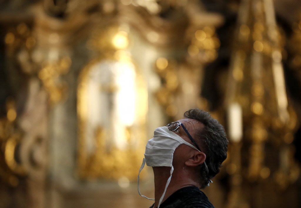 A man wearing a face mask visit the St. Nicholas church in Prague, Czech Republic, Thursday, Sept. 10, 2020. The Czech Republic is returning to mandat...