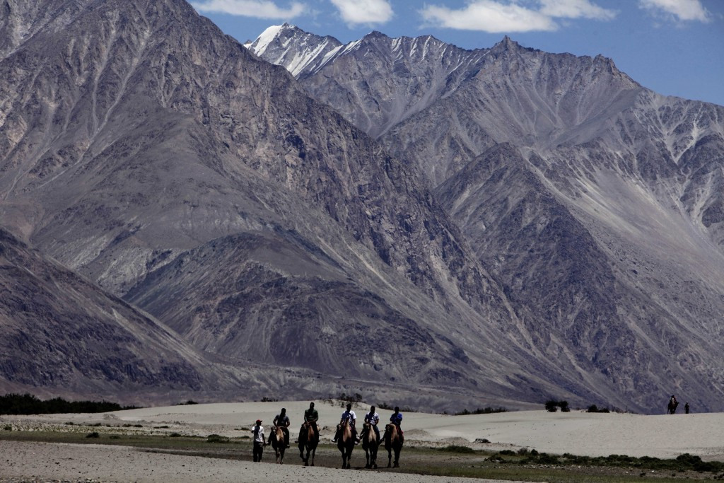 FILE- In this July 20, 2011 file photo, tourists ride double hump camels at Nubra valley, in Ladakh, India. Tensions along the disputed India-China bo...
