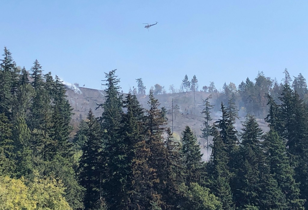 A helicopter flies over fires burning on a ridge in Sumner, Wash., Wednesday, Sept. 9, 2020. Windblown wildfires raging across the Pacific Northwest d...