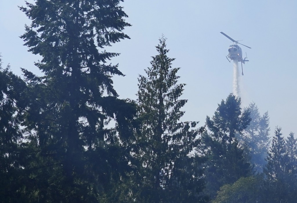 A helicopter makes a water drop, Wednesday, Sept. 9, 2020, on a hotspot of a wildfire burning in Bonney Lake, Wash., south of Seattle. (AP Photo/Ted S...