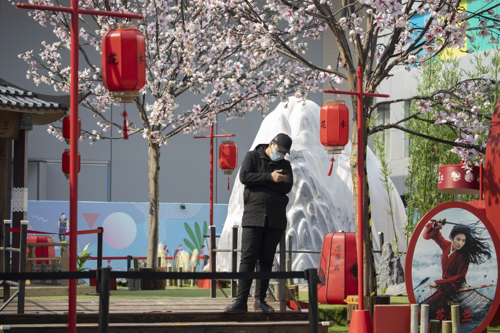 """A man stands in a set promoting the Disney movie """"Mulan"""" in Beijing on Wednesday, Feb. 19, 2020. Disney is under fire for filming part of its live-act..."""