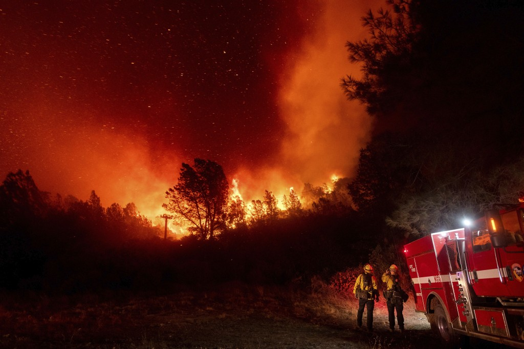 FILE - In this Sept. 9, 2020, file photo, firefighters watch the Bear Fire approach in Oroville, Calif. Climate-connected disasters seem everywhere in...