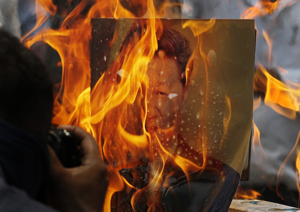 FILE-In this June 22, 2020 file photo, Indian traders burn Chinese products and a poster president Xi Jinping during a protest in New Delhi, India. Te...