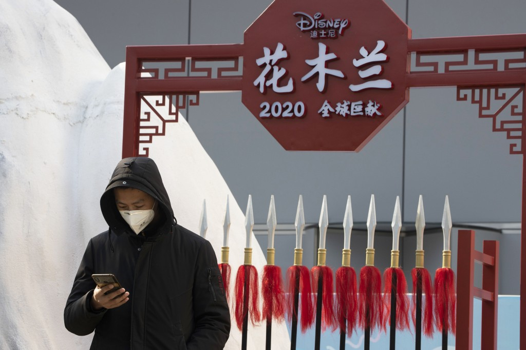 A man stands in a set promoting the Disney movie Mulan in Beijing on Wednesday, Feb. 19, 2020. Disney is under fire for filming part of its live-actio...