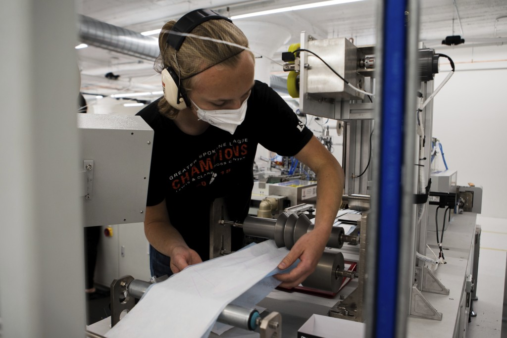 In this undated photo provided by Outdoor Research in September 2020, a worker adjusts material on a machine that makes surgical masks in Seattle. As ...