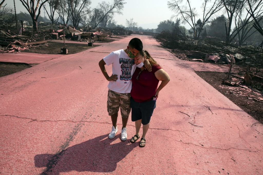 Maria Centeno, right, from Mexico, is consoled by her neighbor Hector Rocha after seeing their destroyed mobile homes at the Talent Mobile Estates, Th...