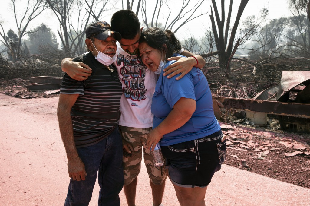 Dora Negrete, right, and her husband Marcelino Rocha, left, and son Hector Rocha console each other after seeing their destroyed mobile home at the Ta...