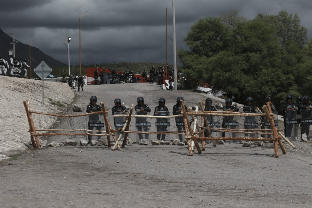 National Guard troops equipped with riot gear stand guard at Las Pilas dam, two days after withdrawing from nearby La Boquilla dam after clashing with...