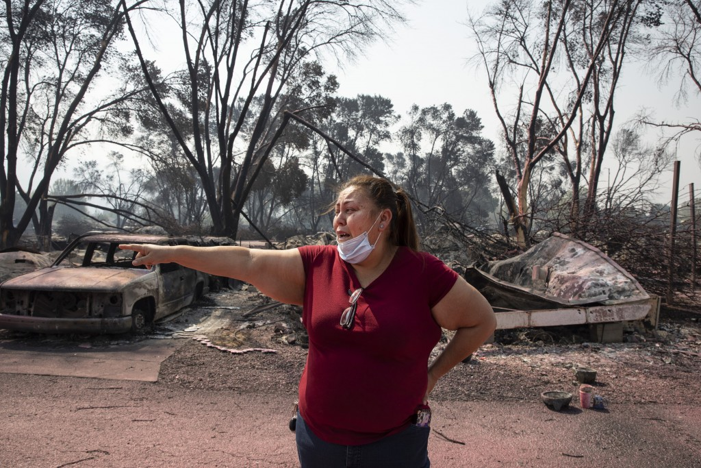 Maria Centeno from Mexico, reacts after seeing her destroyed mobile home at the Talent Mobile Estates as wildfires devastate the region on Thursday, S...