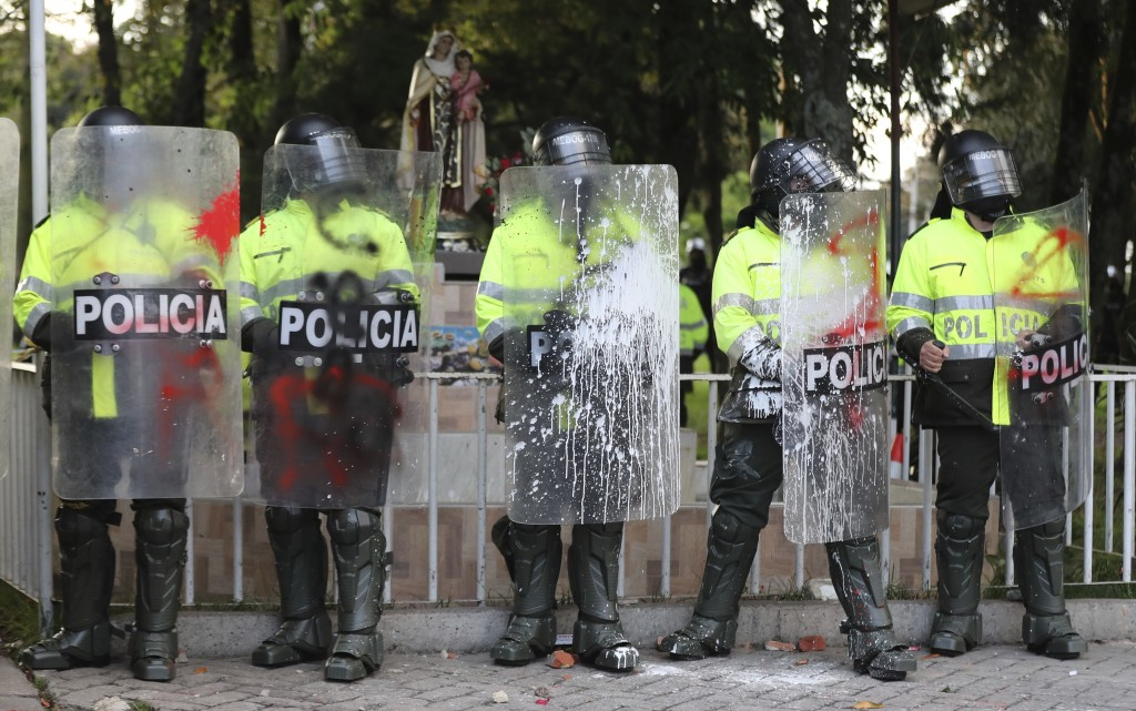 Police stand guard during protests against the death of a man who was detained by police for violating social distancing rules to curb the spread of t...