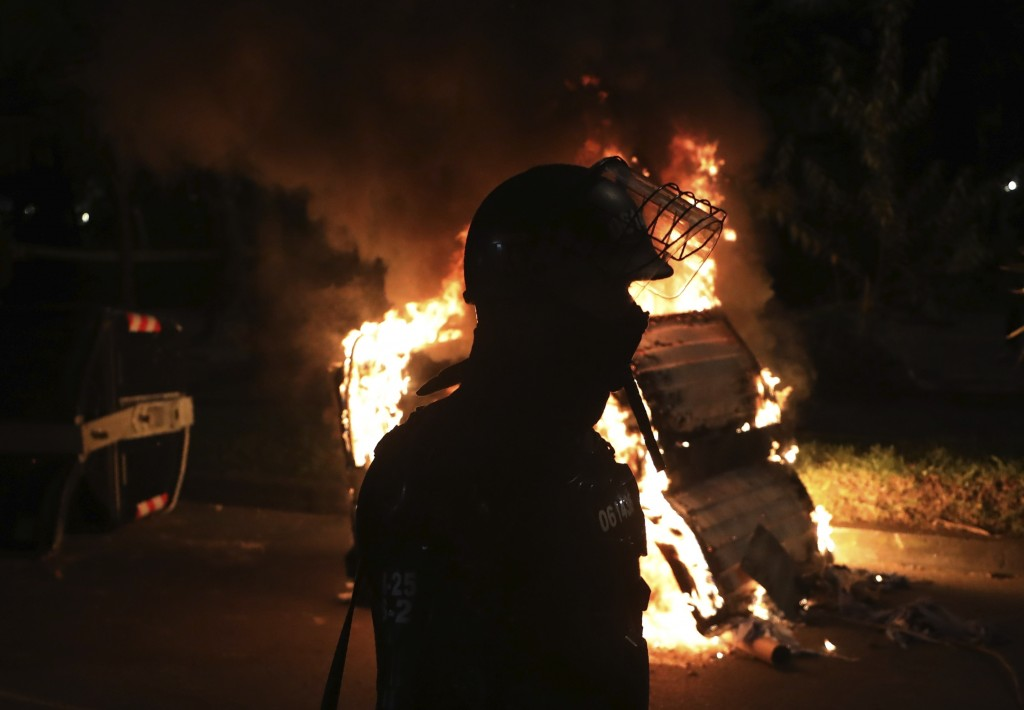 A police officer in riot gear stands behind a burning barricade during protests against the death of a man who was detained by police for violating so...