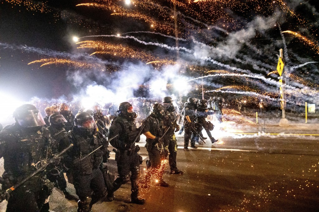 Police use chemical irritants and crowd control munitions to disperse protesters during a demonstration in Portland, Ore., Saturday, Sept. 5, 2020. Hu...