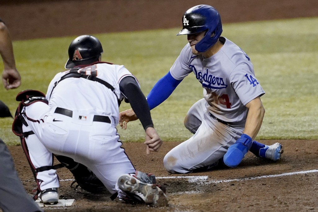 Los Angeles Dodgers' Enrique Hernandez, right, is tagged out trying to steal home by Arizona Diamondbacks catcher Carson Kelly during the sixth inning...