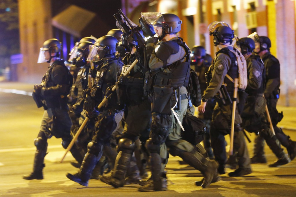 FILE - In this Sunday, May 31, 2020, file photo, police in riot gear advance on protesters as they attempt to clear the streets in Richmond, Va. Virgi...