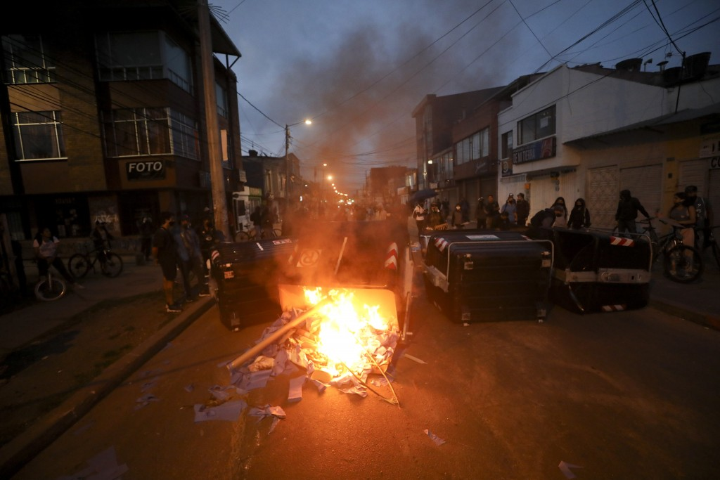 Demonstrators stand behind a garbage bin set on fire during protests against the death of a man who was detained by police for violating social distan...
