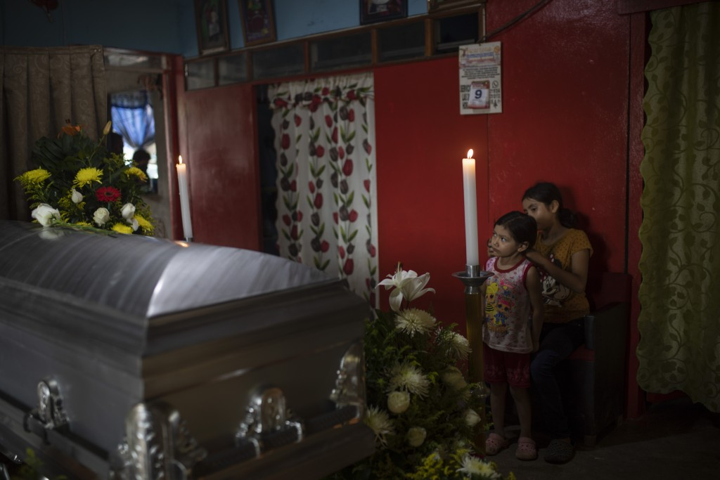 Two of six children of slain journalist Julio Valdivia stand by his casket during a wake inside their home in Tezonapa, Veracruz, Mexico, Thursday, Se...