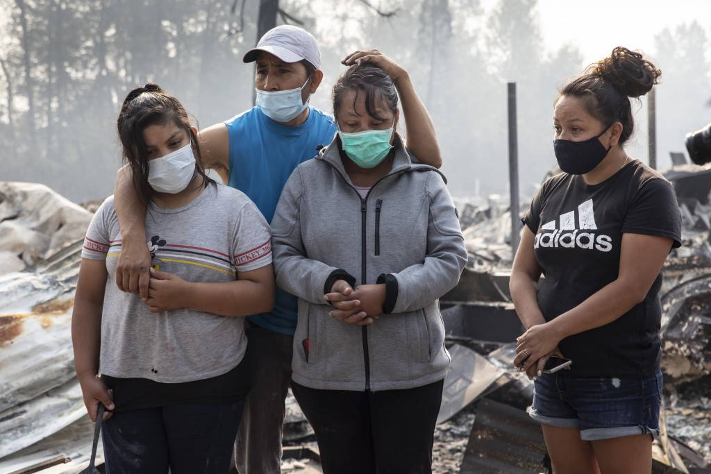 The Reyes family looks at the destruction of their home at Coleman Creek Estates mobile home park in Phoenix, Ore., Thursday, Sept. 10, 2020. The area...