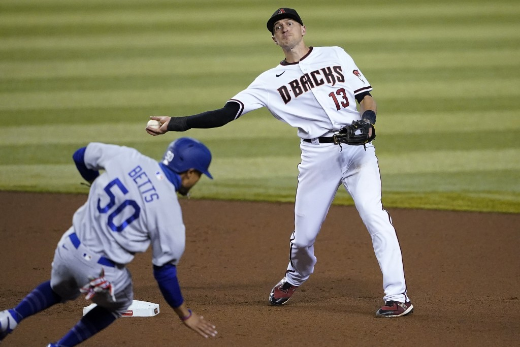 Arizona Diamondbacks' Nick Ahmed (13) forces out Los Angeles Dodgers' Mookie Betts (50) as he turns a double play on Corey Seager during the fourth in...