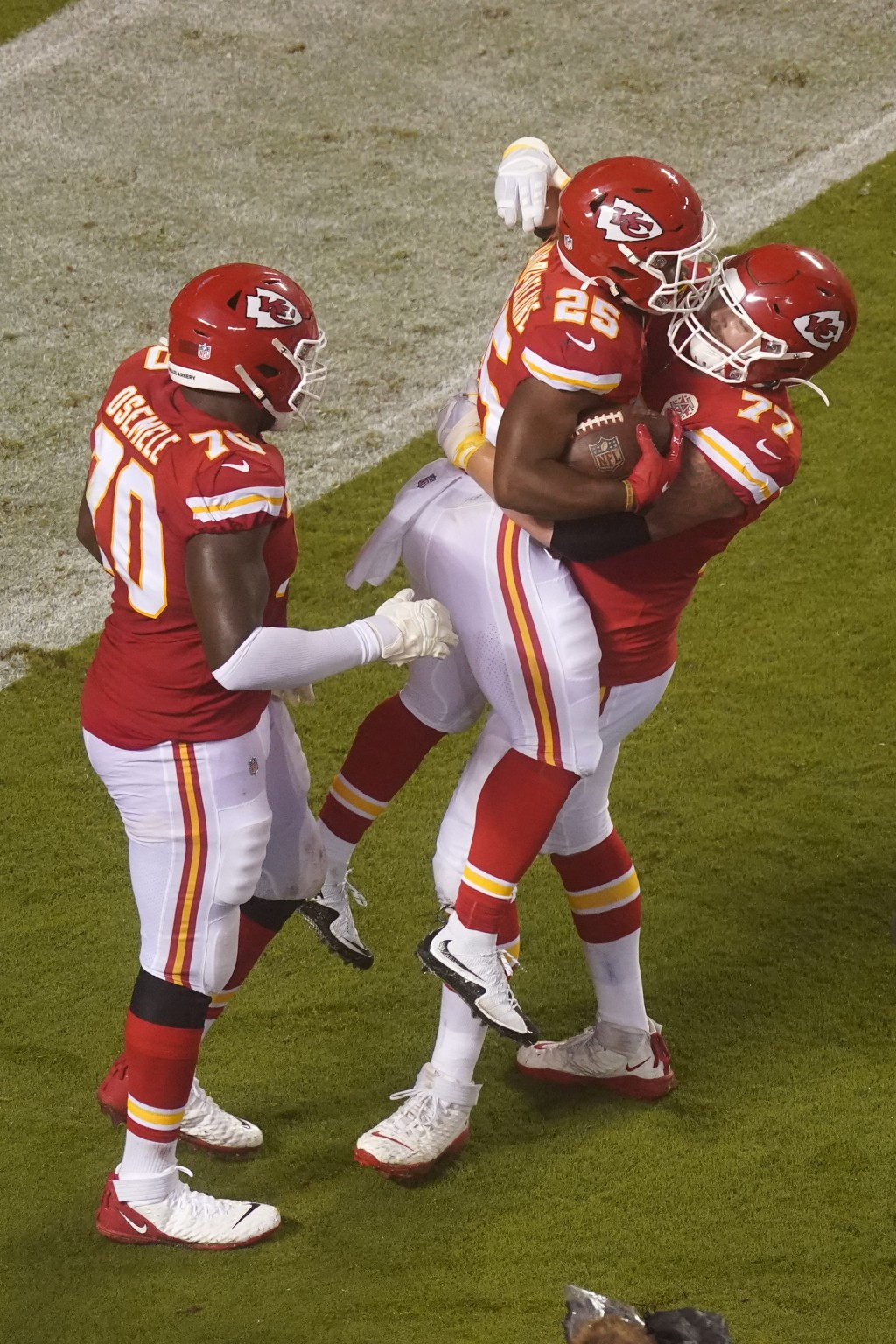 Kansas City Chiefs running back Clyde Edwards-Helaire (25) celebrates with Andrew Wylie (77) and Kelechi Osemele (70) after Edwards-Helaire scored a t...