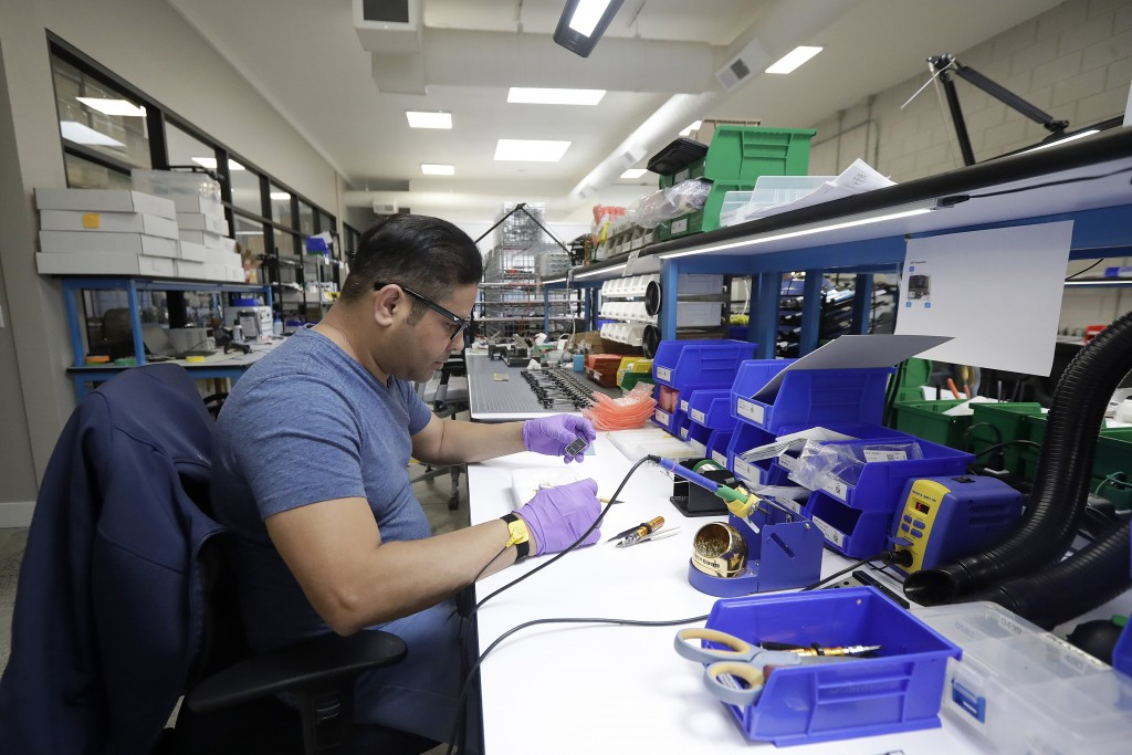 In this June 22, 2018, photo, Skydio tech assembler Alex Nakmoto works on the R1 flying camera drones in a laboratory in Redwood City, Calif. Skateboa...