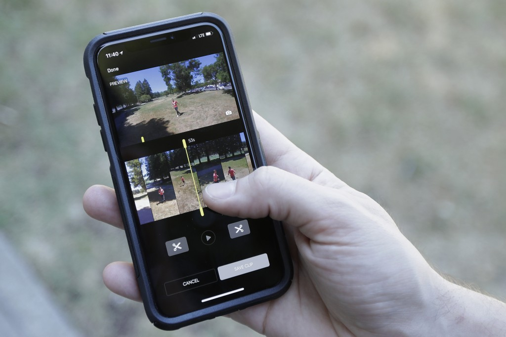 In this June 22, 2018, photo, Skydio head of marketing Patrick Stahl holds his phone showing videography intern Henry Belcaster on the screen as they ...