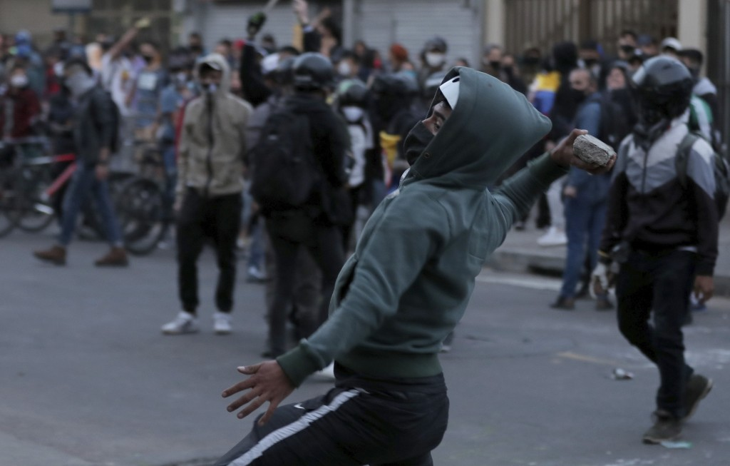 A masked man hurls stones at the police during protests against the death of a man who was detained by police for violating social distancing rules to...