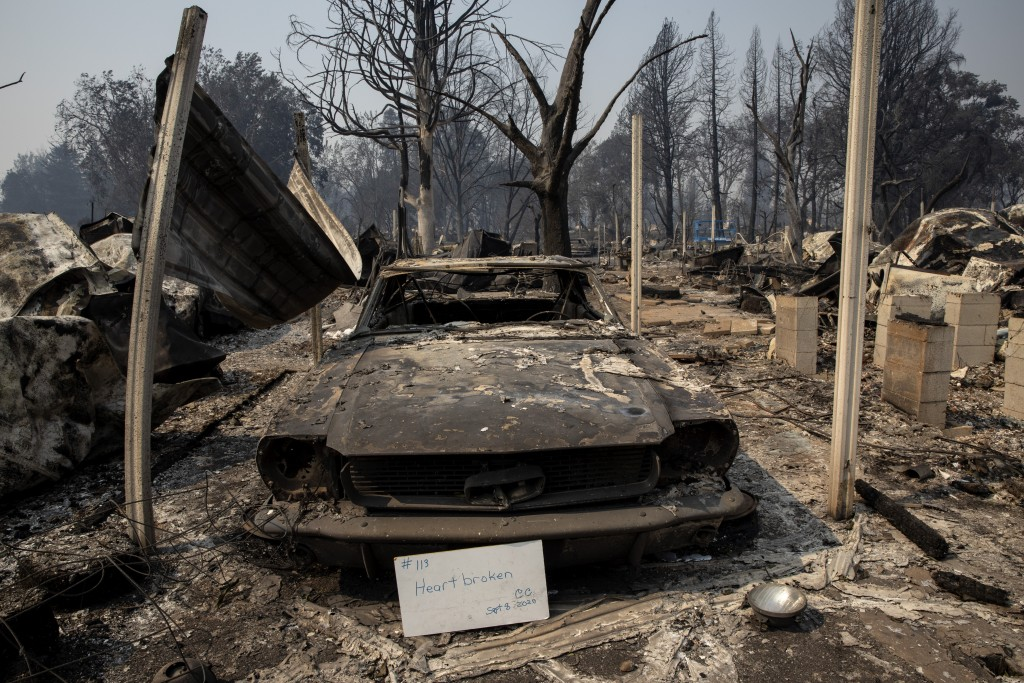 "A sign that reads ""Heart broken"" is displayed in front of a destroyed vehicle at Coleman Creek Estates mobile home park in Phoenix, Ore., Thursday, Se..."