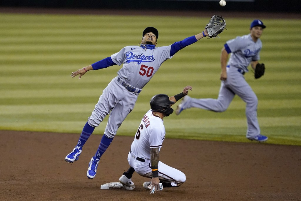 Arizona Diamondbacks' David Peralta (6) advances safely to second on a wild pitch as Los Angeles Dodgers' Mookie Betts (50) can't catch a throwing err...