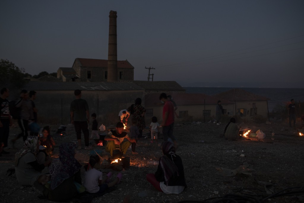 Refugees and migrants cook on makeshift fires near an abandoned factory in the island of Lesbos, Greece, Friday, Sept. 11, 2020.  Some thousands of re...