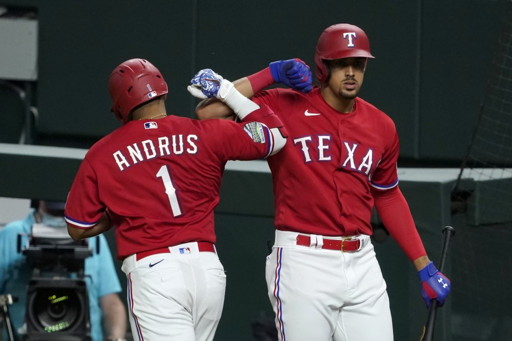 Texas Rangers' Elvis Andrus (1) celebrates his solo home run with Ronald Guzman, right, in the seventh inning of a baseball game against the Oakland A...