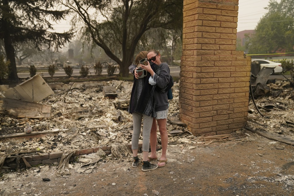 Desiree Pierce, right, hugs her step daughter Leah Johnson as they visit their home destroyed by the Almeda Fire, Friday, Sept. 11, 2020, in Talent, O...
