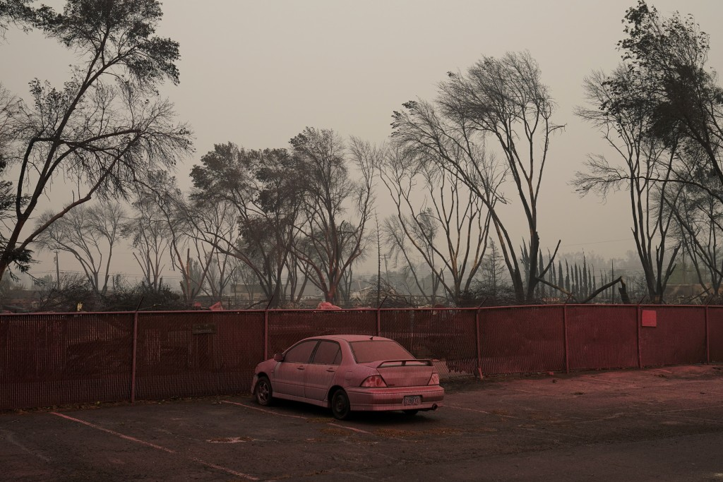Pink fire retardant covers a car in an area destroyed by the Almeda Fire, Friday, Sept. 11, 2020, in Talent, Ore. (AP Photo/John Locher)