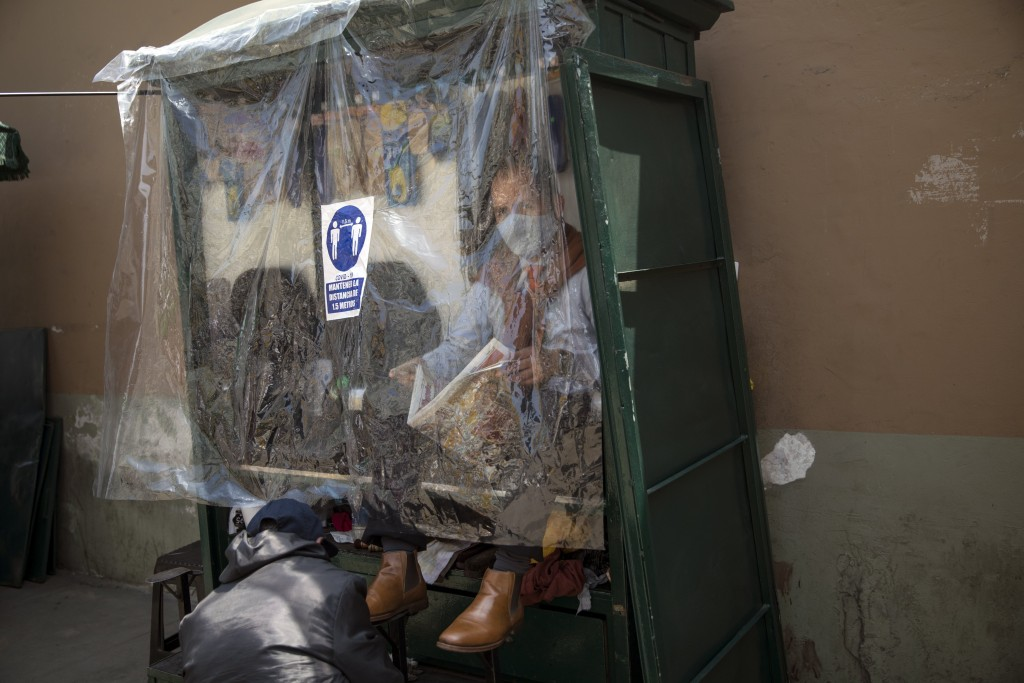 A man reads a newspaper as he gets his shoes shined, behind a plastic sheet due to the COVID-19 pandemic, near Congress in Lima, Peru, Friday, Sept. 1...