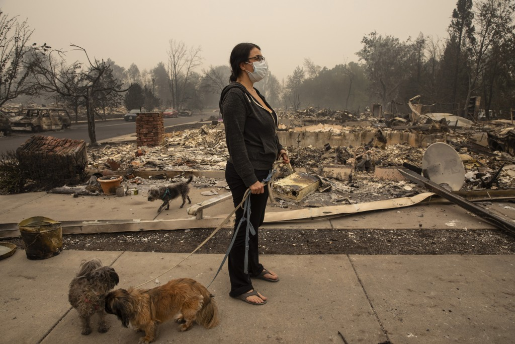 Lexi Sovllios from Talent, Ore., holds her dogs as she looks at the ruins of her burned house in Talent on Friday, Sept. 11, 2020, as destructive wild...