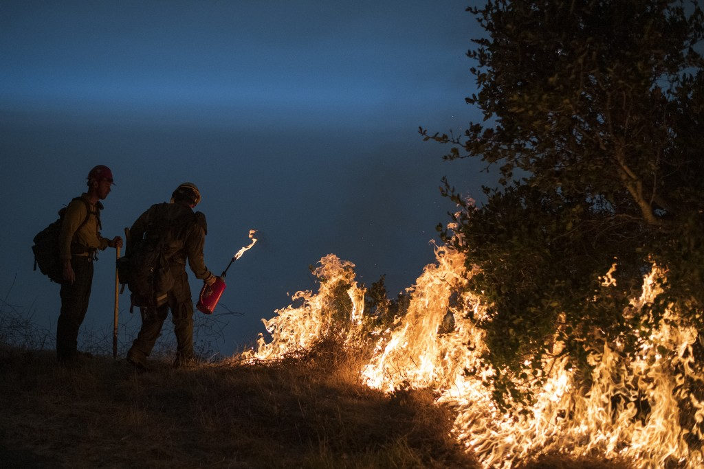 Firefighters light a controlled burn along Nacimiento-Fergusson Road to help contain the Dolan Fire near Big Sur, Calif., Friday, Sept. 11, 2020. (AP ...