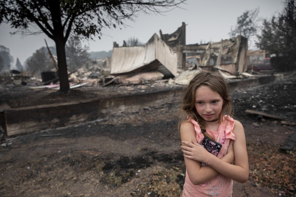 Ellie Owens, 8, from Grants Pass, Ore., looks at fire damage Friday, Sept. 11, 2020, as destructive wildfires devastate the region in Talent, Ore. (AP...