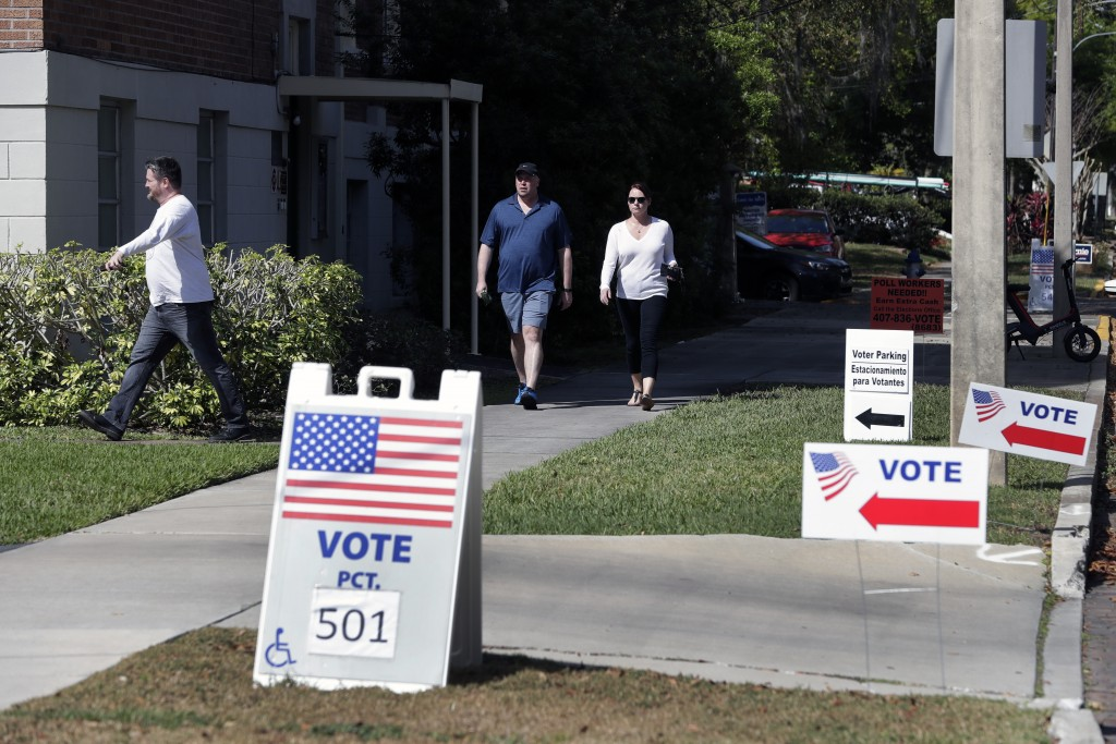 FILE - In this March 17, 2020 file photo, voters head to a polling station to vote in Florida's primary election in Orlando, Fla.    Florida felons mu...