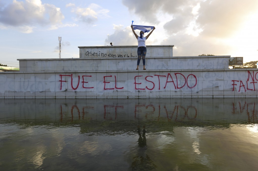 """FILE - In this June 1, 2018 file photo, a masked protestor holds up a Nicaraguan flag above the Spanish graffiti phrase: """"The state did it,"""" during a ..."""