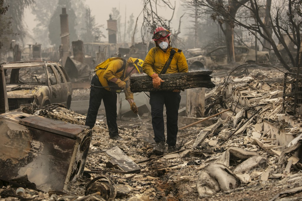 Jackson County District 5 firefighter Captain Aaron Bustard, right, and Andy Buckingham work on a smoldering fire in a burned neighborhood as destruct...